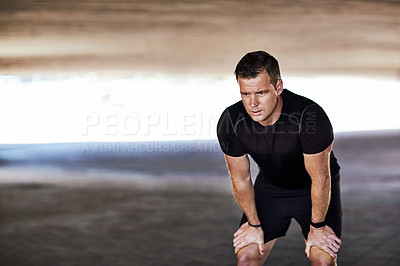 Buy stock photo Full length shot of a handsome young male athlete resting while working out in the city