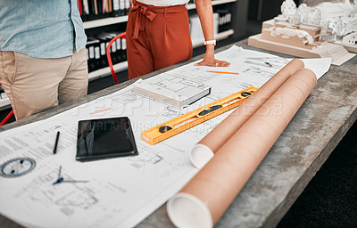 Buy stock photo Cropped shot of two unrecognizable architects working with blueprints in a modern office