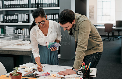Buy stock photo Cropped shot of two aspiring young architects working together in a modern office