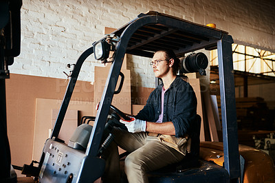 Buy stock photo Shot of a handsome young man driving a forklift inside a warehouse