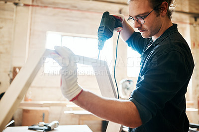 Buy stock photo Shot of a handsome young carpenter using an electric drill while working inside a workshop