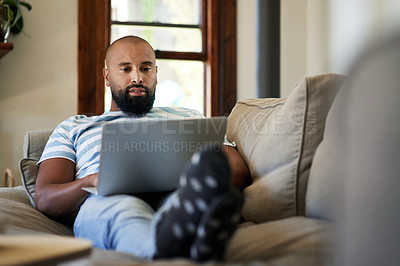 Buy stock photo Shot of a handsome young man using a laptop while relaxing in his living room at home