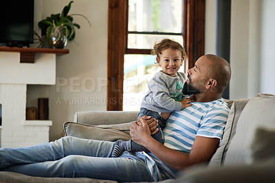 Buy stock photo Cropped shot of an adorable little boy smiling while spending time with his dad in their living room at home