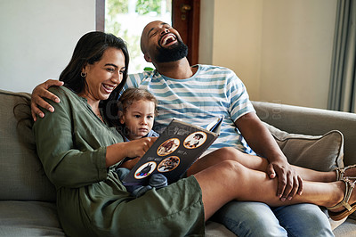 Buy stock photo Cropped shot of an affectionate young couple laughing while reading a picture book with their little son at home