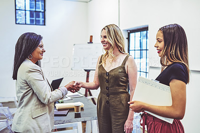 Buy stock photo Shot of businesswomen shaking hands in an office