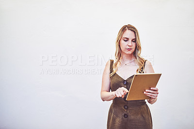 Buy stock photo Studio shot of a young businesswoman using a digital tablet against a white background