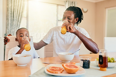 Buy stock photo Cropped shot of a happy father and son bonding over breakfast  and enjoying a glass of fruit juice at home