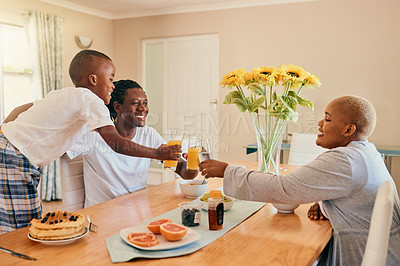 Buy stock photo Cropped shot of a happy young family sitting together and bonding over breakfast during a weekend at home