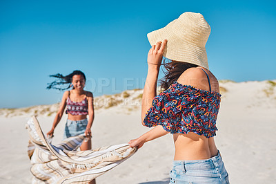 Buy stock photo Shot of two attractive young women setting up to have a picnic together on the beach