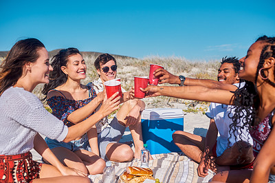 Buy stock photo Shot of a group of young friends sharing a toast and having a picnic together at the beach