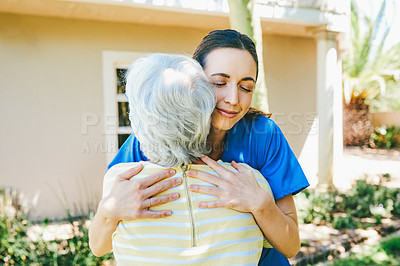 Buy stock photo Cropped shot of an attractive young female nurse hugging a senior woman outdoors at a nursing home