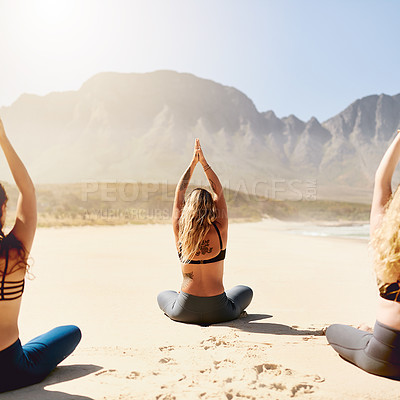 Buy stock photo Rearview shot of three young women practising yoga on the beach