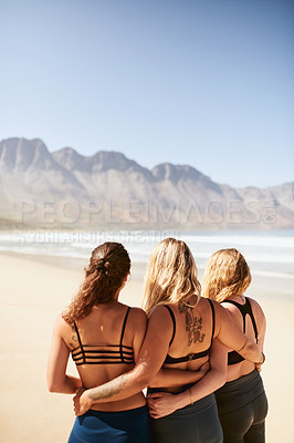 Buy stock photo Rearview shot of three young yogis standing on the beach