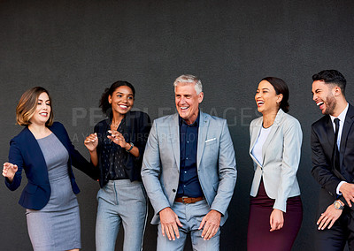 Buy stock photo Cropped shot of a diverse group of businesspeople feeling playful and dancing together against a gray background outside