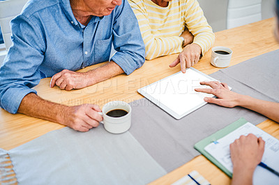 Buy stock photo Cropped shot of an unrecognizable senior couple using a digital tablet while consulting with their financial advisor at home