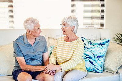 Buy stock photo Shot of a senior couple having a serious conversation on the sofa at home