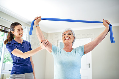 Buy stock photo Shot of a physiotherapist assisting a senior woman with a resistance band