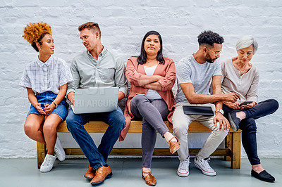 Buy stock photo Full length shot of a diverse group of businesspeople sitting together and using technology in the office