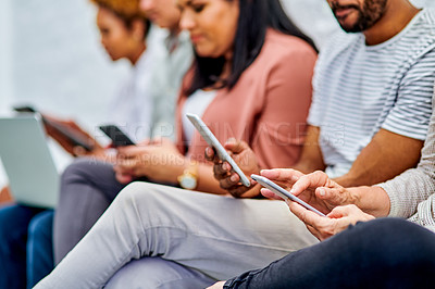 Buy stock photo Cropped shot of an unrecognizable group of businesspeople sitting together and using technology in the office