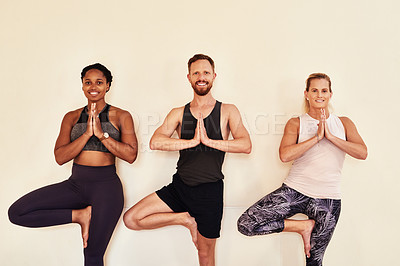 Buy stock photo Shot of a group of young men and women practicing the tree pose during a yoga session