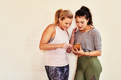 Buy stock photo Shot of two young women using a smartphone during a yoga class