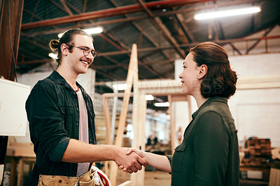 Buy stock photo Cropped shot of two young carpenters shaking hands while working together inside their workshop