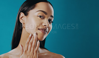Buy stock photo Shot of a beautiful young woman touching her face against a blue background