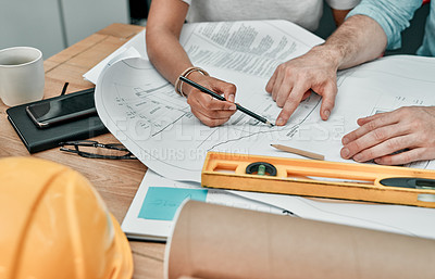 Buy stock photo Closeup shot of two architects working with blueprints in an office