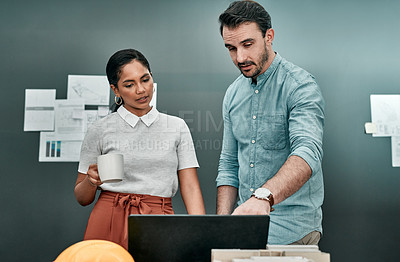 Buy stock photo Shot of two architects working together on a laptop in an office