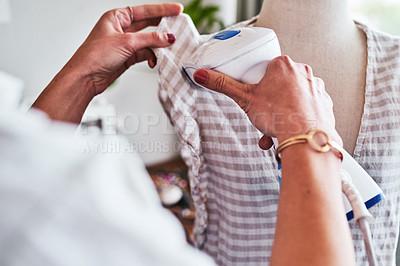 Buy stock photo Shot of a fashion designer using  a garment steamer in her workshop