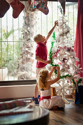 Buy stock photo Full length shot of two adorable young siblings decorating a Christmas tree together at home