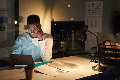 Buy stock photo Shot of a young businessman looking tired while using a digital tablet during a late night at work