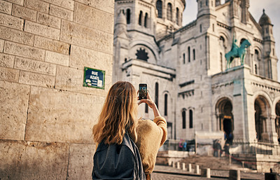 Buy stock photo Cropped shot of an unrecognizable woman standing and using a cellphone to take pictures while sightseeing in Paris