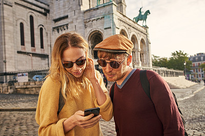 Buy stock photo Cropped shot of a happy young couple standing together and using a cellphone while sightseeing in Paris