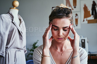 Buy stock photo Cropped shot of a fashion designer looking stressed at her desk