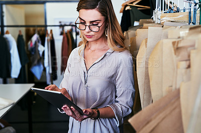 Buy stock photo Cropped shot of a young fashion designer using a digital tablet at work