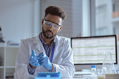 Buy stock photo Shot of a young scientist putting on surgical gloves in a lab
