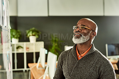 Buy stock photo Cropped shot of a handsome mature businessman standing alone and reading a white board in the office