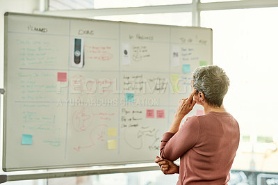 Buy stock photo Cropped shot of an unrecognizable  businesswoman standing alone and looking contemplative while reading a white board in the office