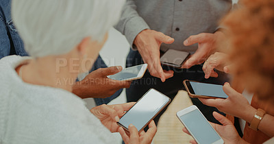 Buy stock photo Cropped shot of a group of businesspeople using their smartphones together at work