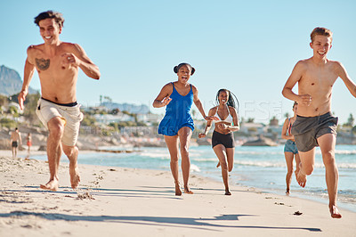 Buy stock photo Shot of a group of friends running together on the beach