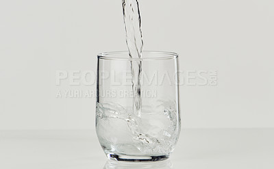 Buy stock photo Cropped shot of an unrecognizable person pouring water in a glass on the tabletop of an empty kitchen