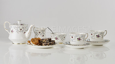 Buy stock photo Cropped shot of tea set with cake and biscuits on a saucer in an empty studio during the day