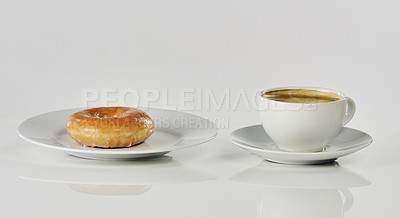 Buy stock photo Cropped shot of coffee and a glazed donut on a saucer in an empty studio during the day