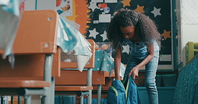 Buy stock photo Shot of a young girl packing her bag and leaving the classroom