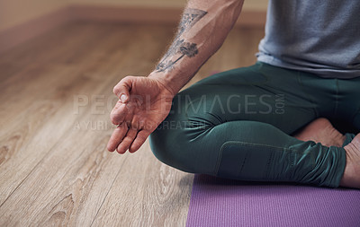 Buy stock photo Cropped shot of an unrecognizable man sitting indoors alone and meditating with his hand in a gyan mudra