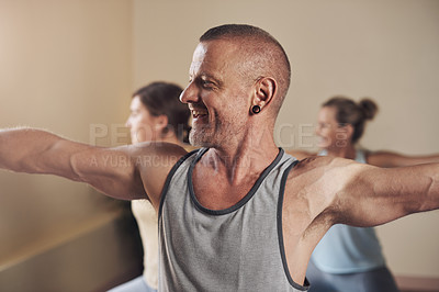 Buy stock photo Cropped shot of a handsome young man holding a warrior two pose during an indoor yoga class