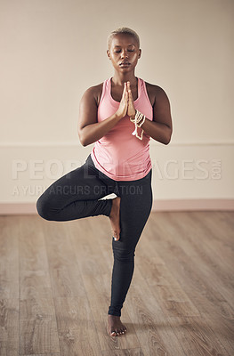 Buy stock photo Full length shot of an attractive young woman holding a tree pose while doing yoga alone indoors