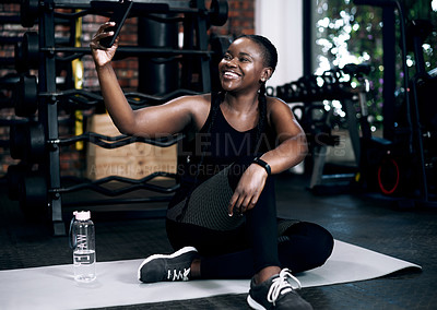 Buy stock photo Full length shot of an attractive young female athlete taking a selfie while sitting on her towel in the gym