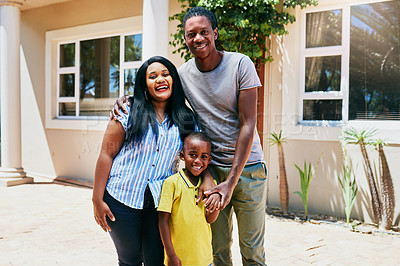 Buy stock photo Cropped portrait of a happy young family of three standing in front of their new home during the day